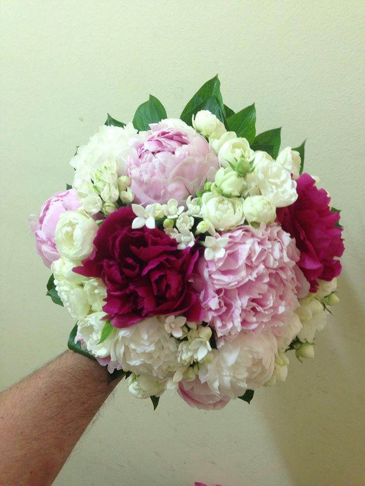 Piccolo centro floreale in colori bianco,rosa e rosso granato con un tocco verde