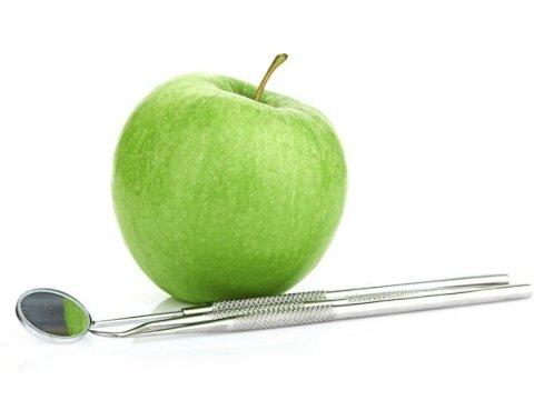 specchietto odontoiatrico e mela verde