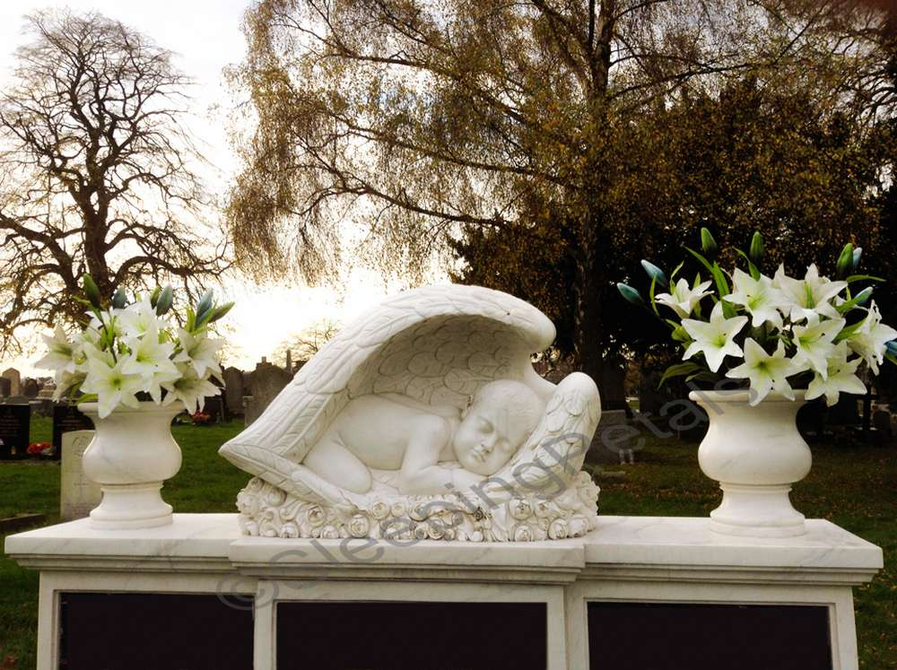 White sleeping angel grave statue between two flower urns