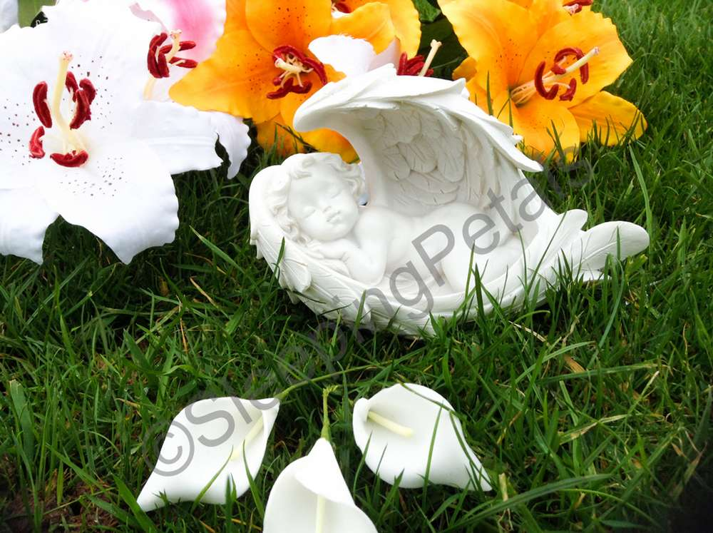White sleeping angel grave statue on grass with artificial flowers