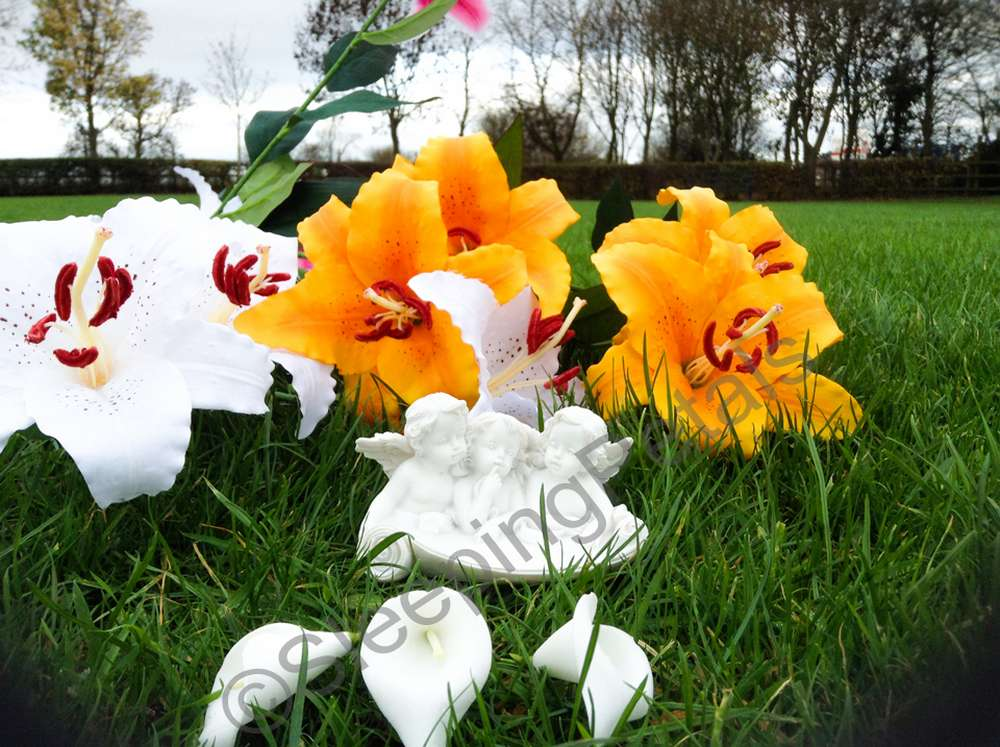 three angel white statue on grass with artificial greave flower bouquet