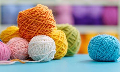 Knitting filo sul tavolo blu contro sfondo sfocato. Primo piano di multi palline di lana colorati