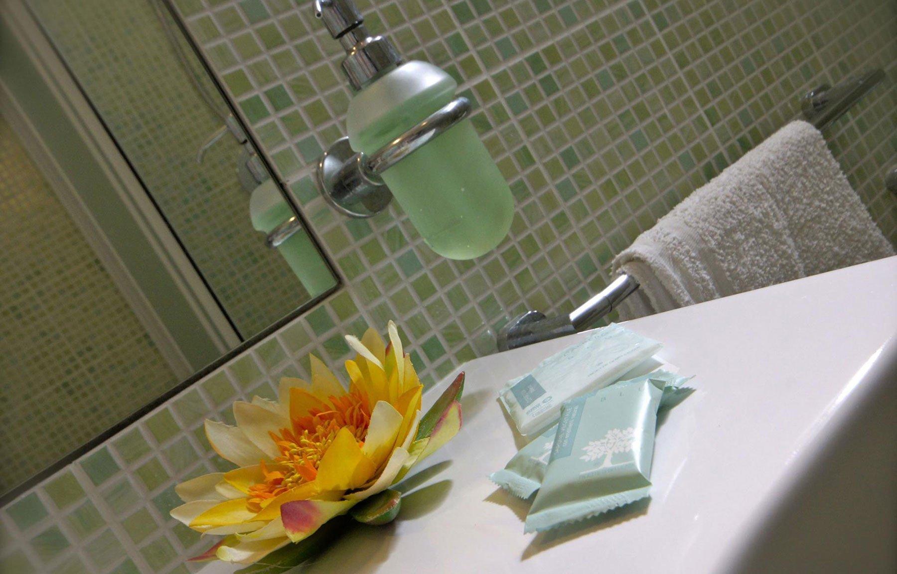 Sala da bagno di piastrelle verde,asciugamani, saponi e un fiore di loto