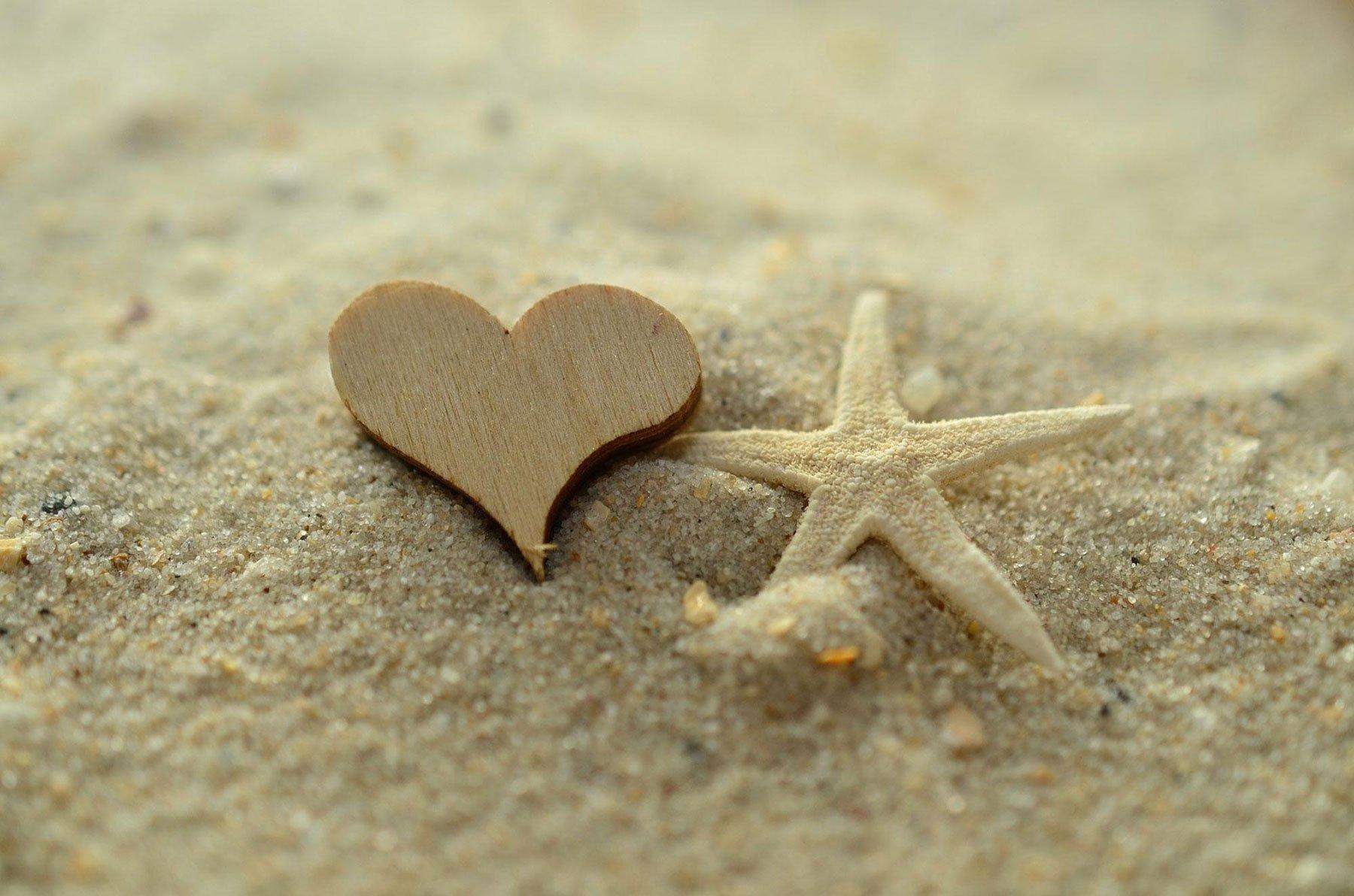 Una stella di mare e un cuore di legno nella sabbia