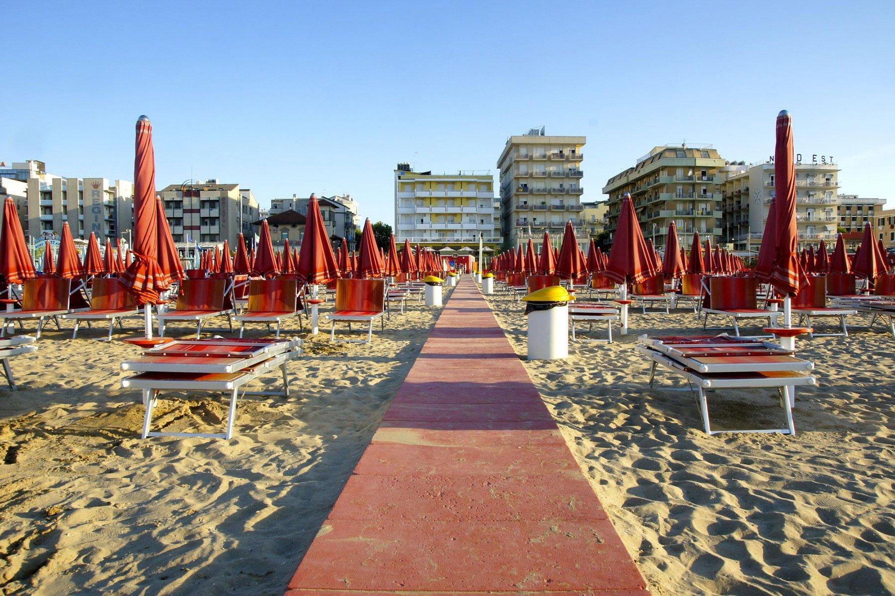 Spiaggia piena di sedie a sdraio e ombrelloni