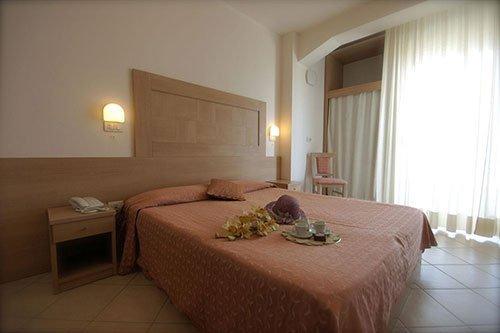 Camera da letto matrimoniale, capello,fiori e due tazze di caffè sul letto