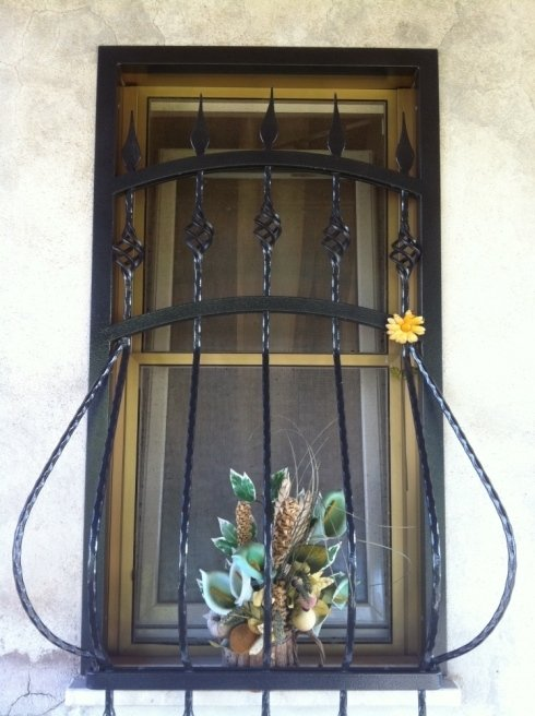 Grata fissa in ferro bombata decorata con lance nella parte superiore.