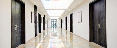 un lungo corridoio e delle porte nere