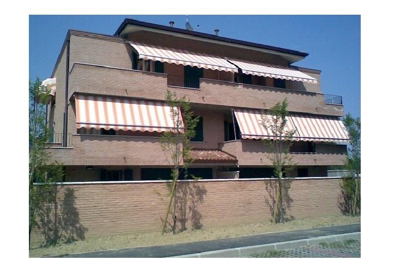 una villa con due piani con delle tende da sole sui balconi