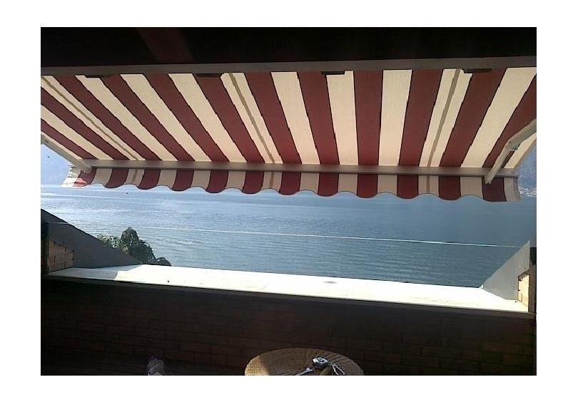 una terrazza con una tenda da sole e vista del lago