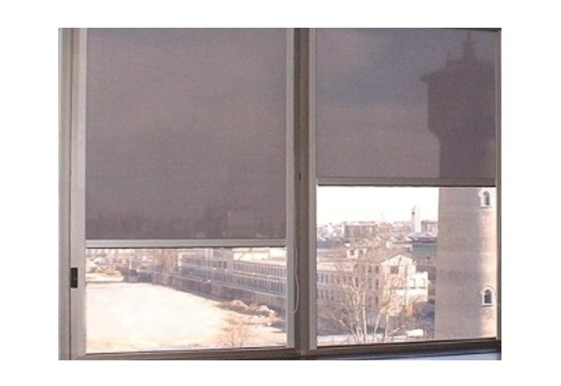 una finestra con delle tende a pannello di color grigio