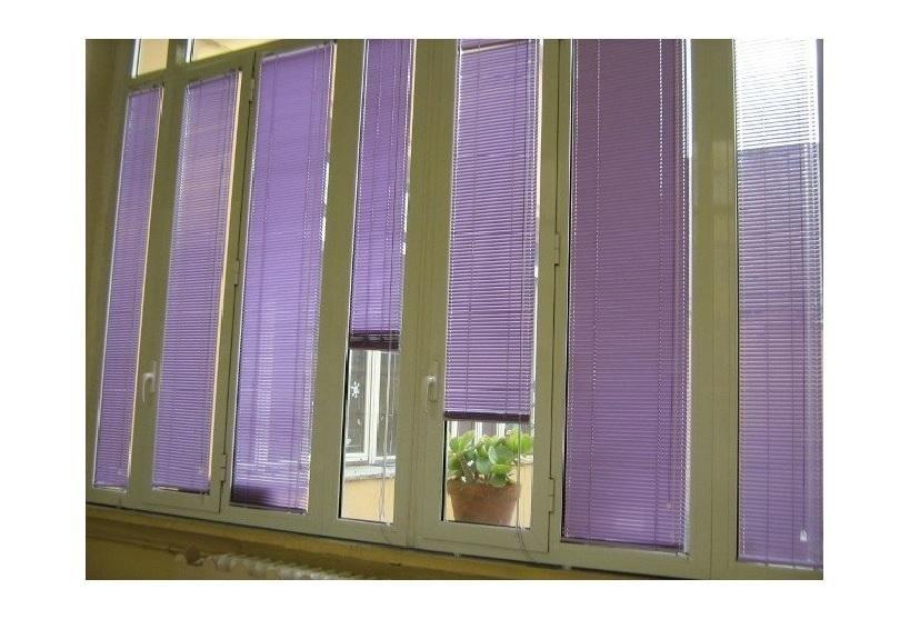 un balcone con delle tende a pacchetto di color viola