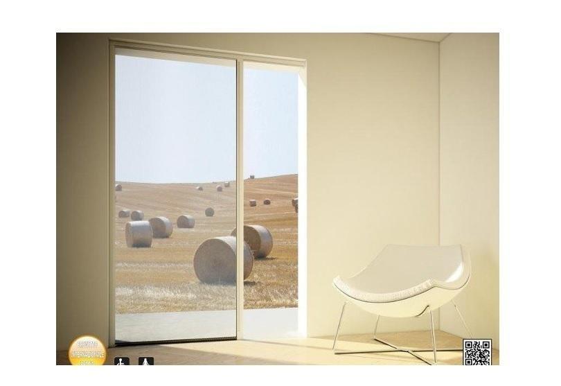 una stanza con una finestra con vista di un terreno con rotule di fieno