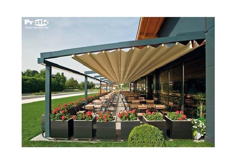 dei tavoli all'esterno di un  ristorante sotto delle tende da sole