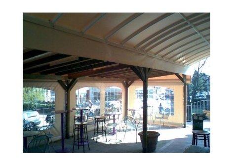 dei tavoli sotto una pergola con colonne di legno
