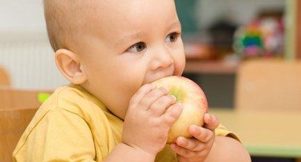 a child biting an apple