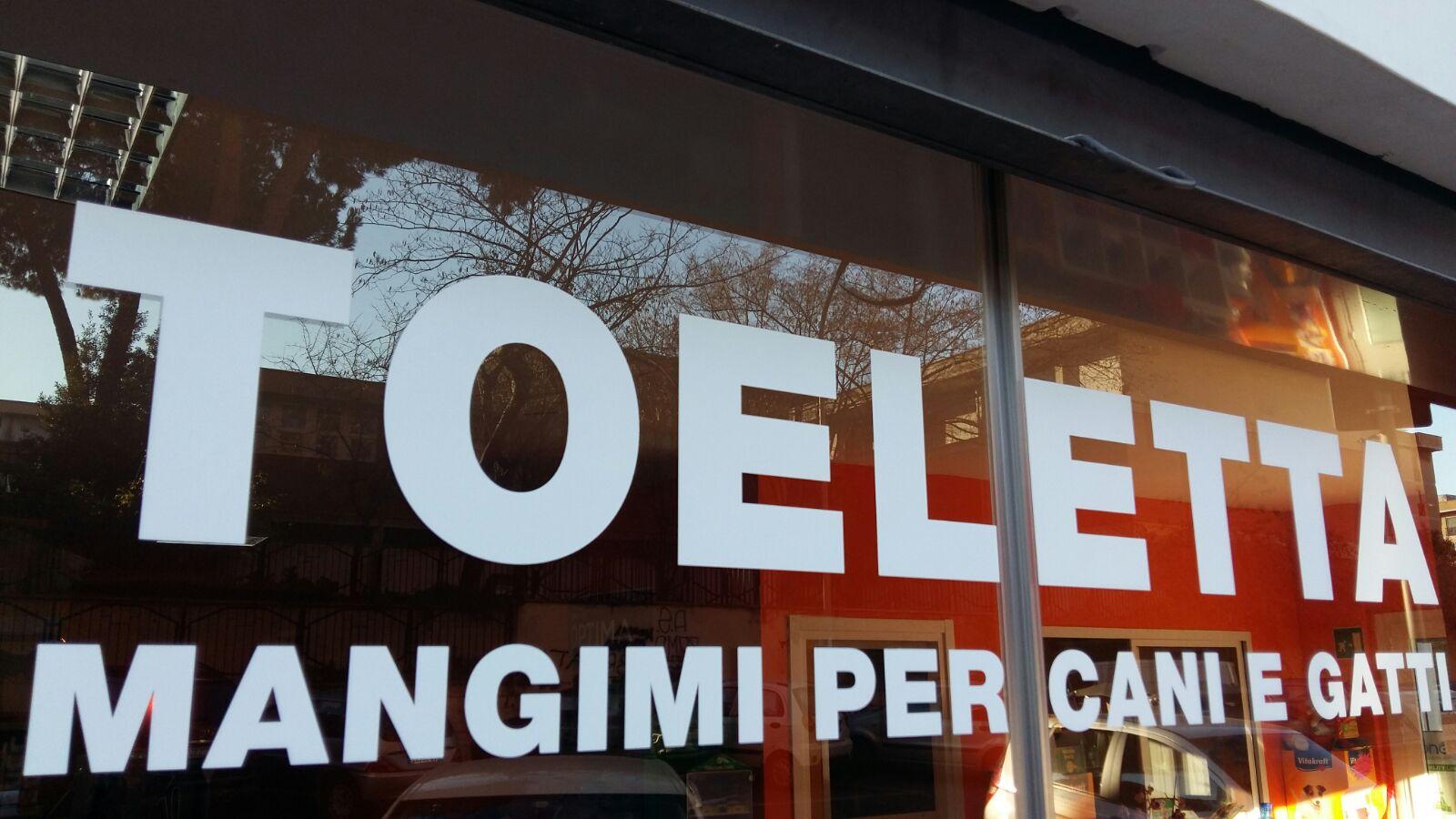 Due vetrine con una scritta in grande Toeletta Mangime per Cani e Gatti
