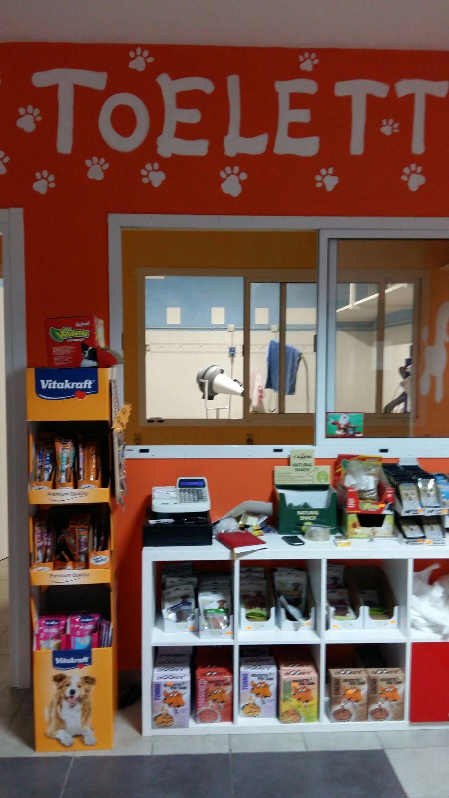 Uno stand con scritto Vitakraft un mobile bianco con altro mangime per animali e attraverso una finestra vista di una stanza per toelettatura degli i animali