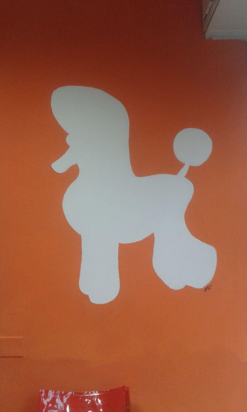 un muro dipinto in arancione e un'immagine raffigurante un cane barboncino