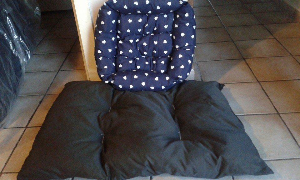 Una cuccia di color blu con cuoricini e un cuscino grande di color nero
