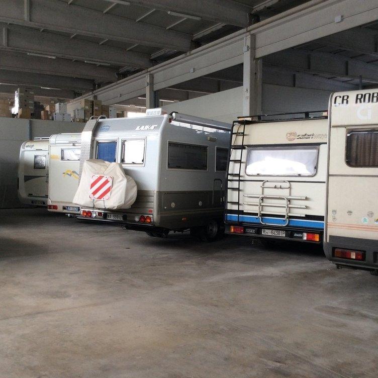 cinque roulotte parcheggiate viste dal dietro all'interno di una rimessa