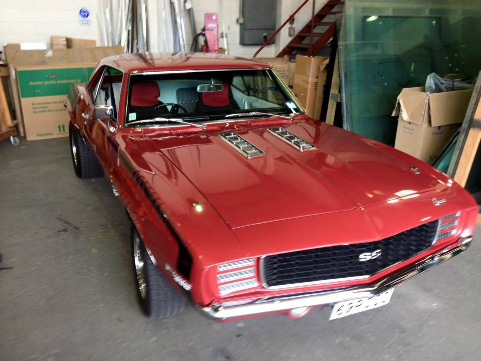 classic ruby red car in garage with new window glazing