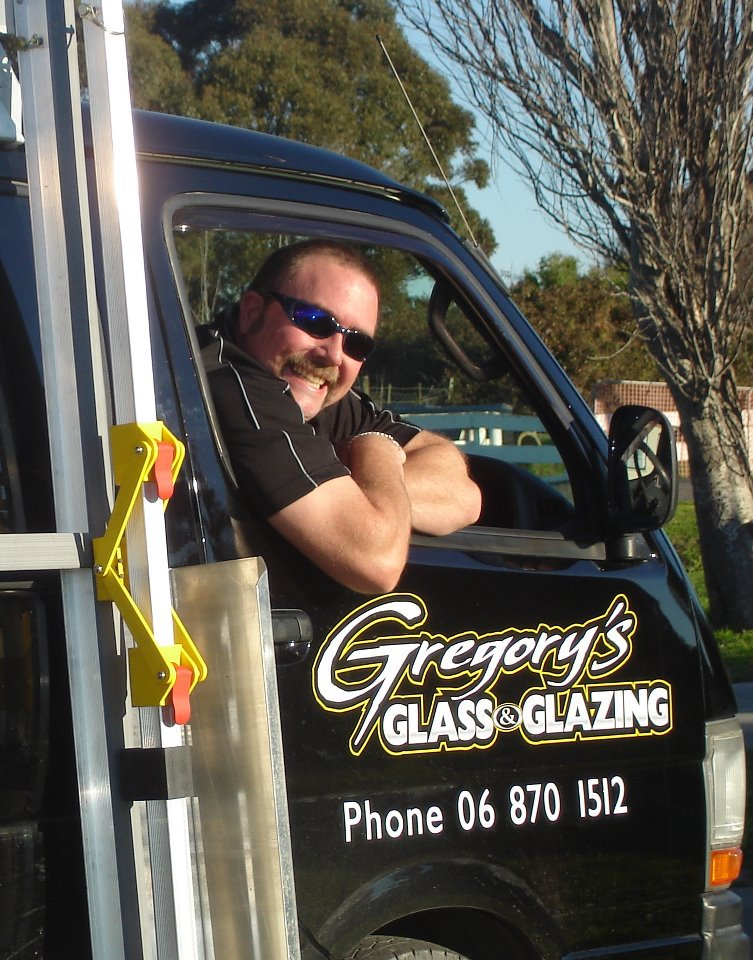 gregorys glass and glazing workman in repair truck smiling out of window