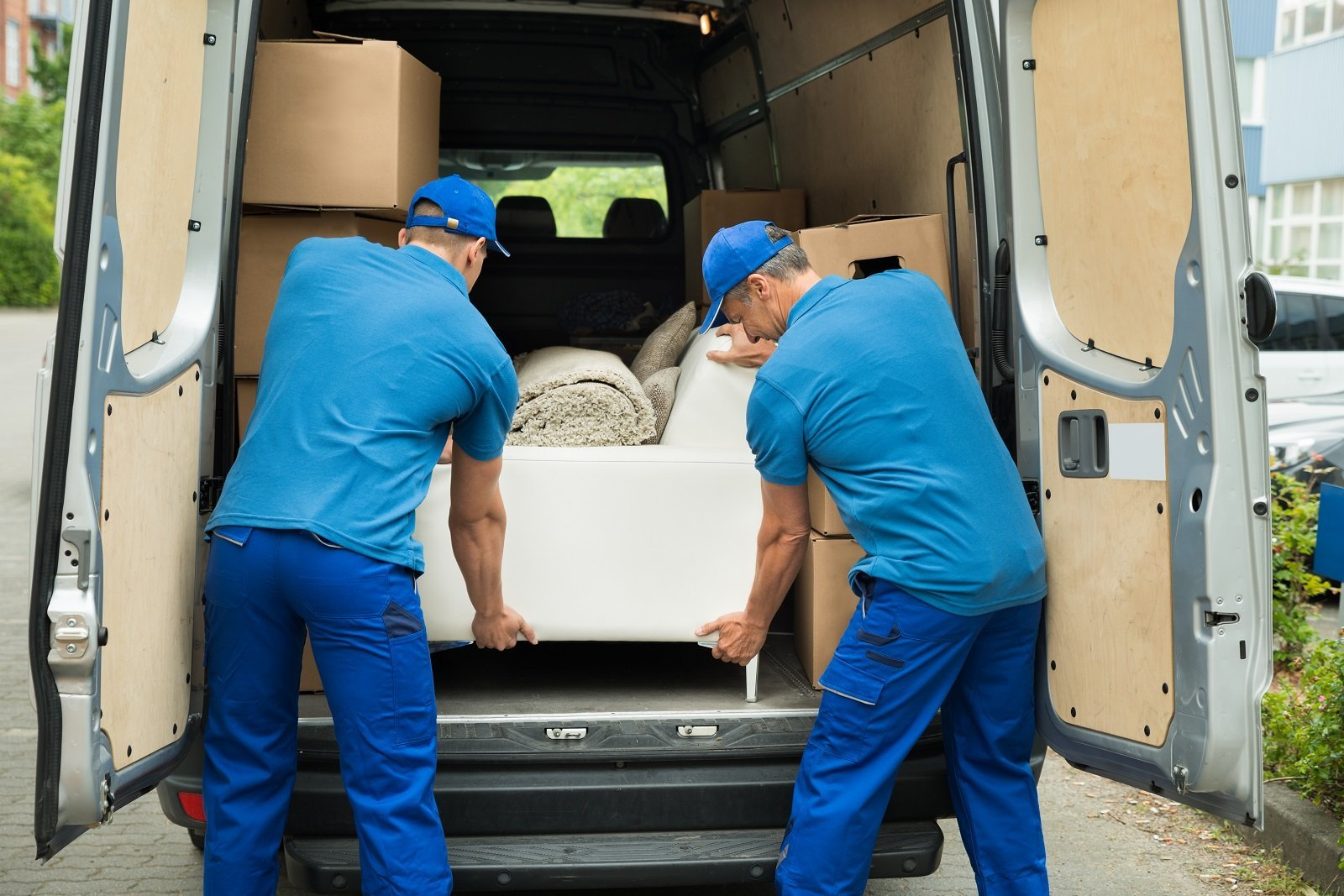 due uomini che caricano un divano su un furgone bianco