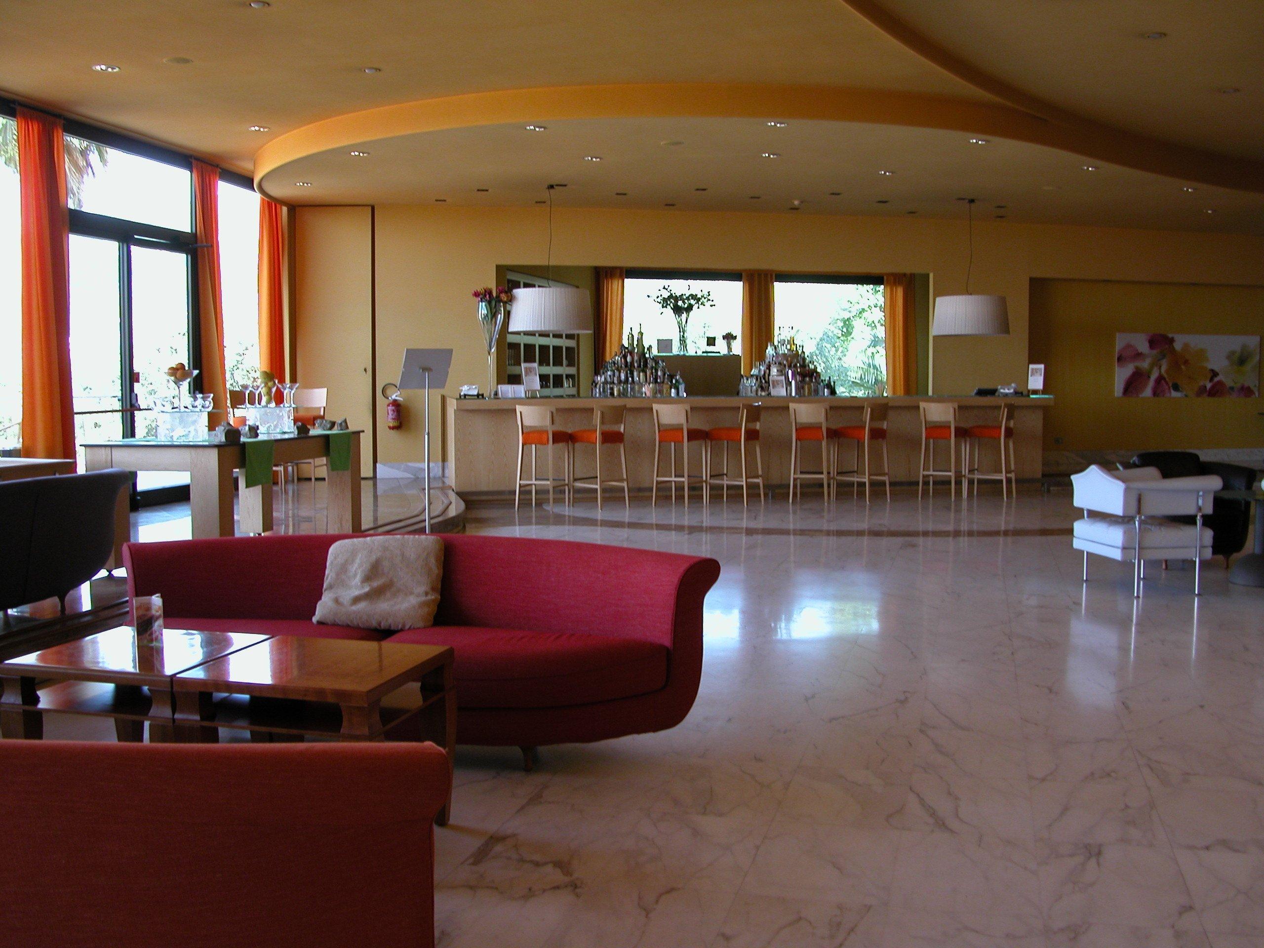 Bar interno di un hotel elegante con divanetti rossi