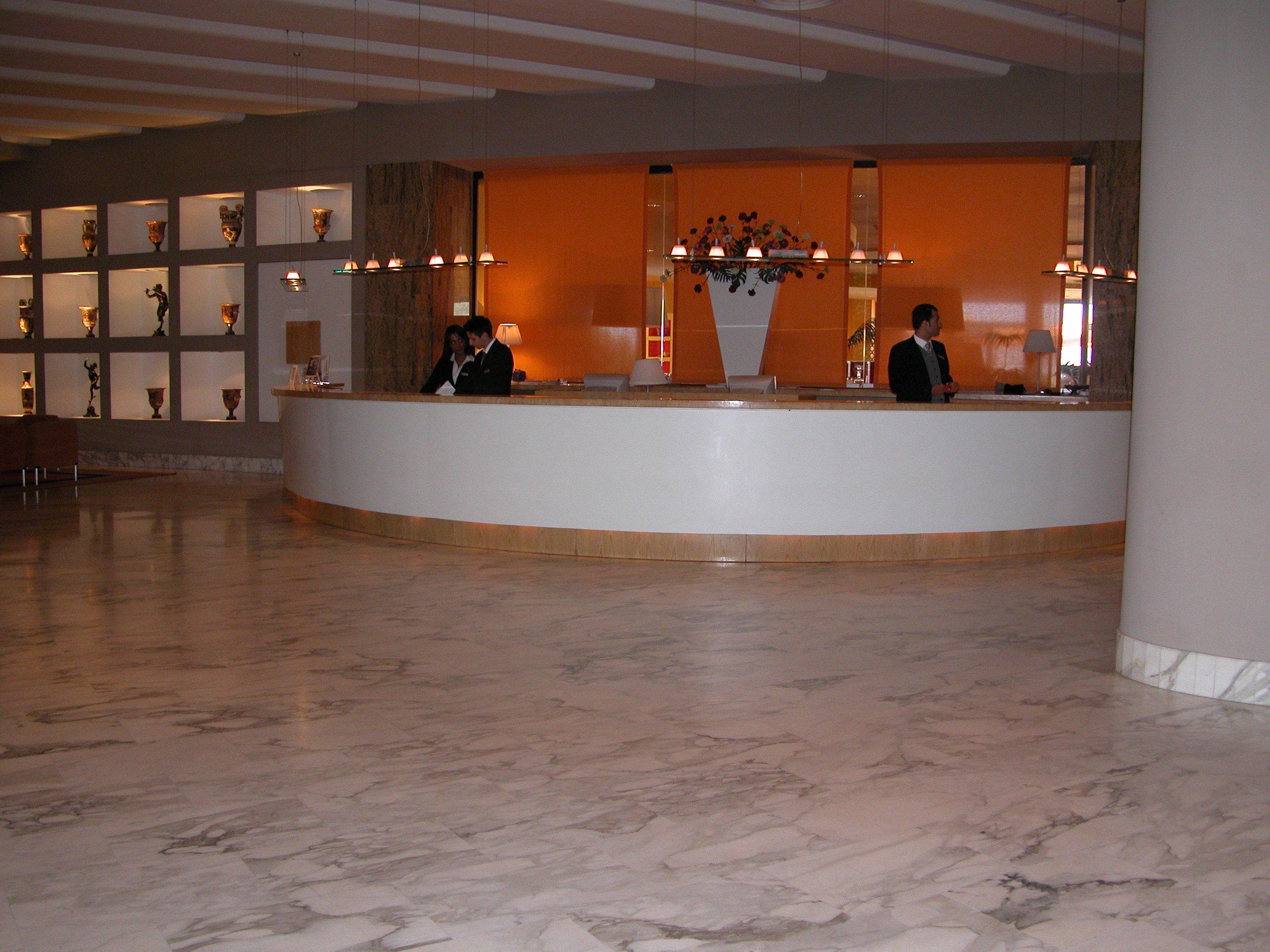 Reception di un hotel elegante con bancone e receptionist dietro