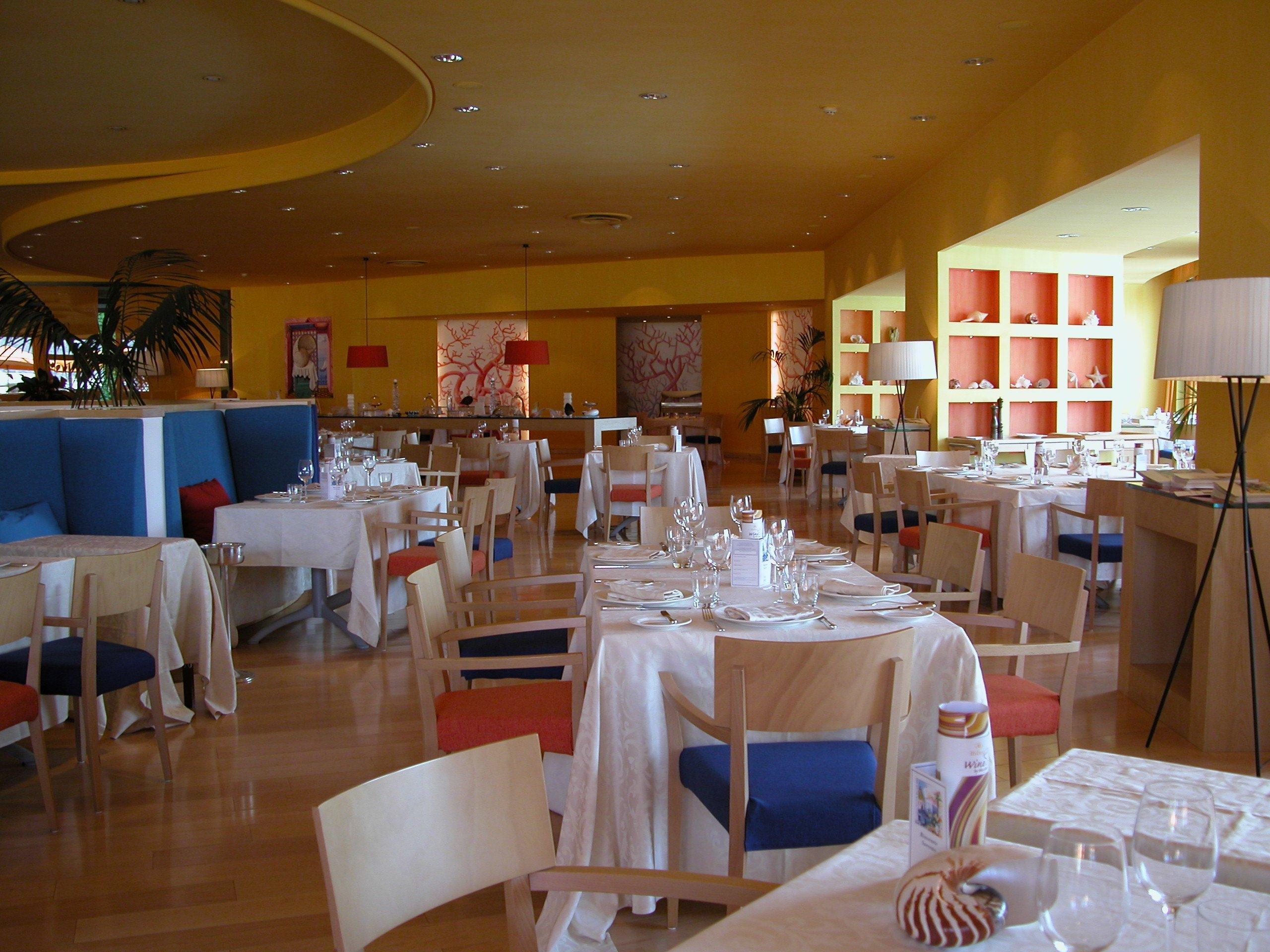 Interno di un ristorante d'hotel con tanti tavoli apparecchiati