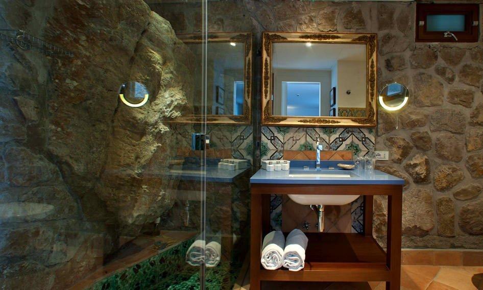 Elegante box doccia creato nella roccia, lavabo con specchio e finestra in stile oblò