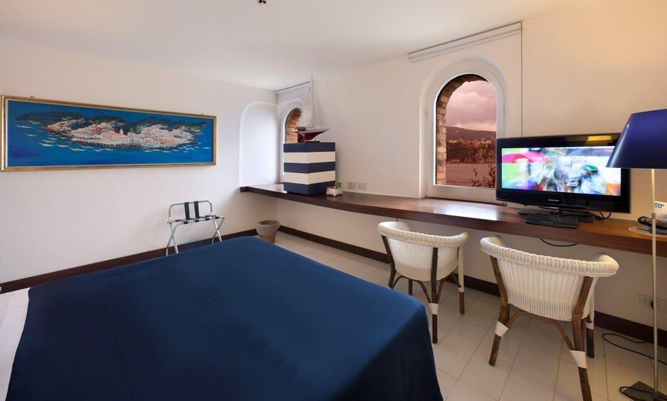 Suite moderna a tinte blu con finestre, letto e scrivania