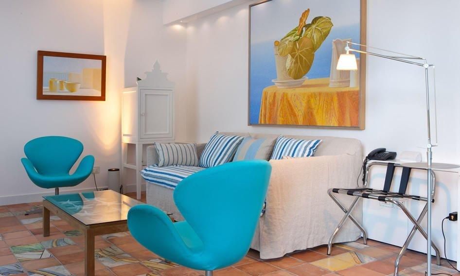 Soggiorno con divano, poltroncina e tavolino in vetro