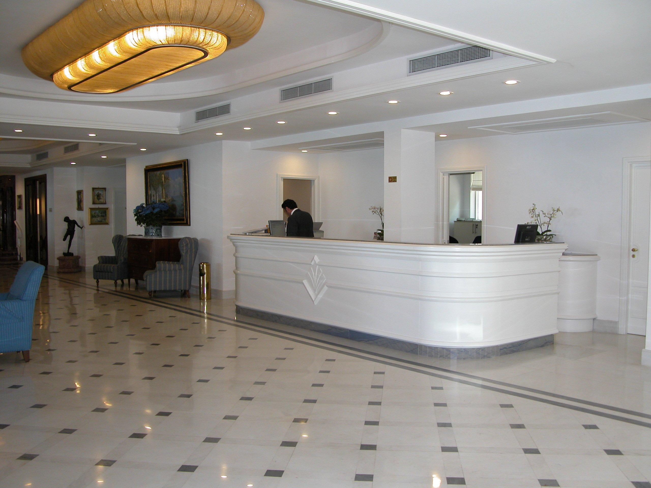 Reception di un hotel elegante di colore bianco con pavimento in marmo a scacchi, bancone con dietro il receptionist in primo piano