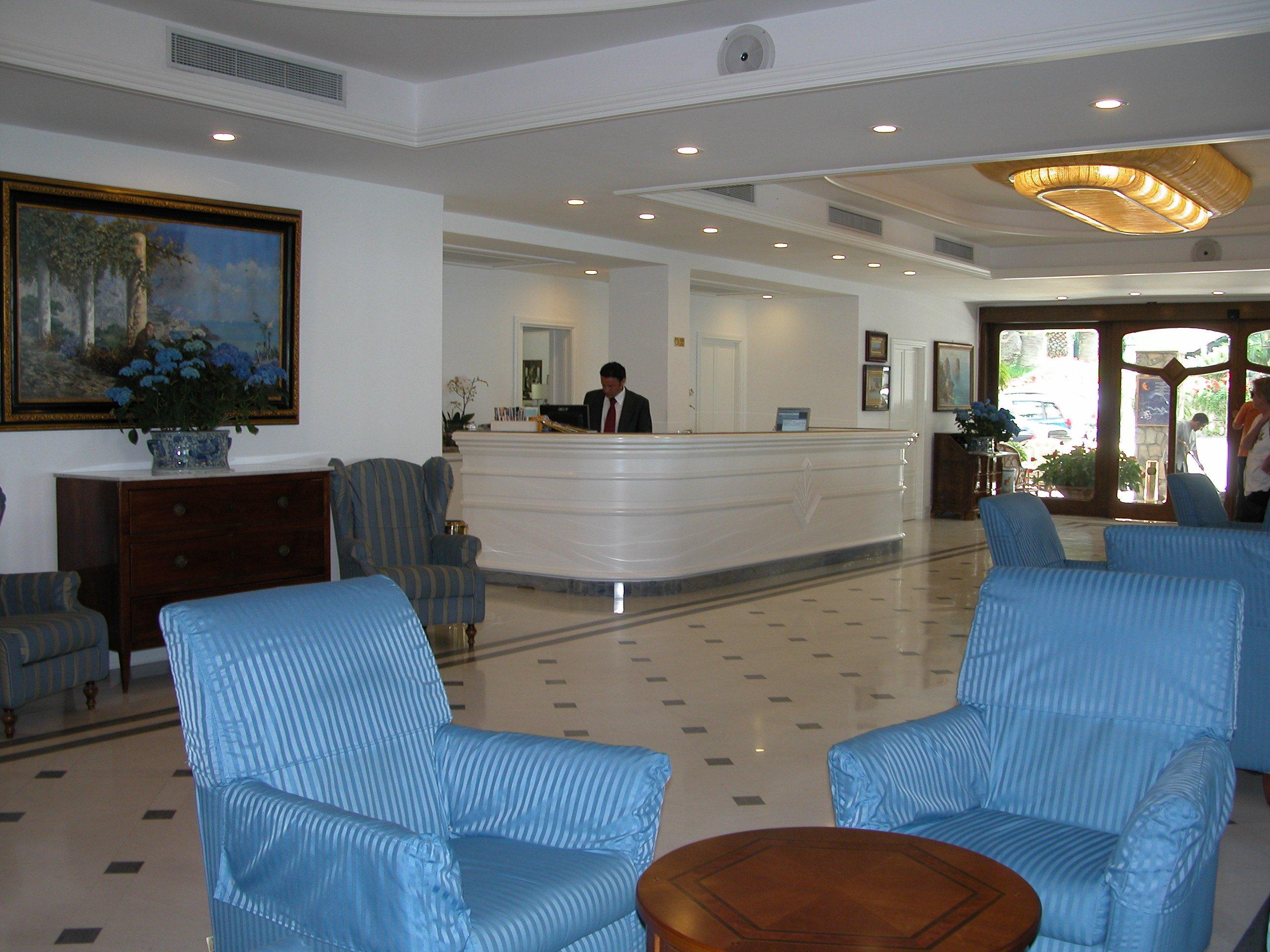 Reception di un hotel elegante di colore bianco con pavimento in marmo a scacchi, un tavolino e due poltrone blu