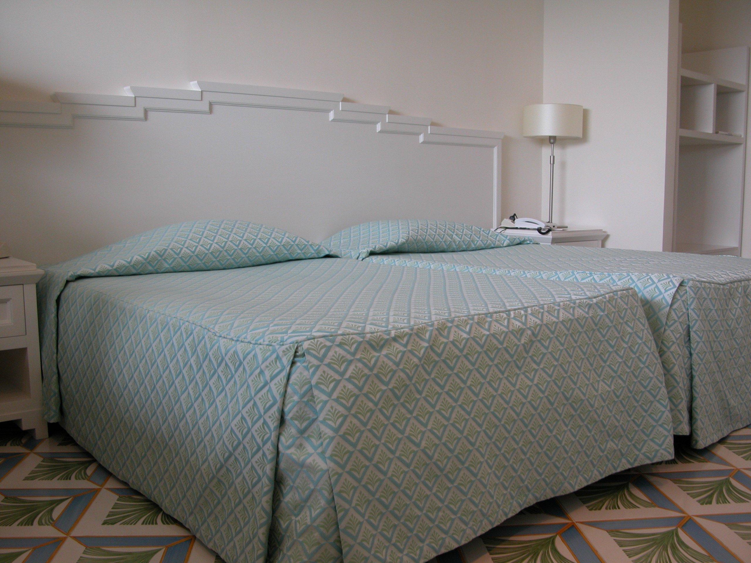 Due ampi letti singoli eleganti con capezzale bianco e coperte azzurro/grigio