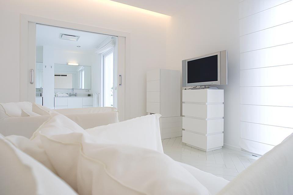 Interno dell'ampia suite minimal con televisione a schermo piatto