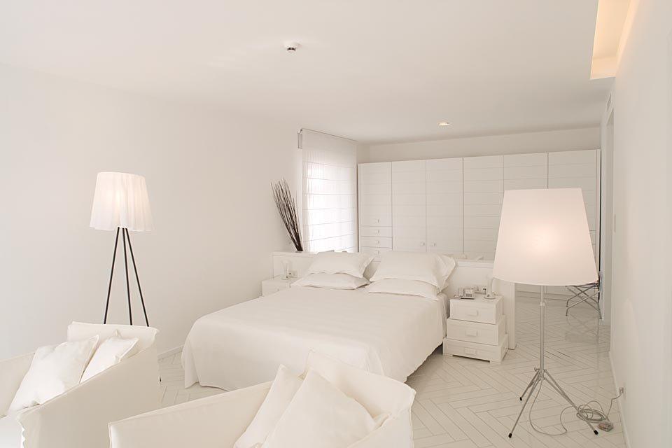Suite minimal bianca con lampade accese