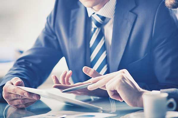 due uomini in giacca e cravatta mentre utilizzano un tablet