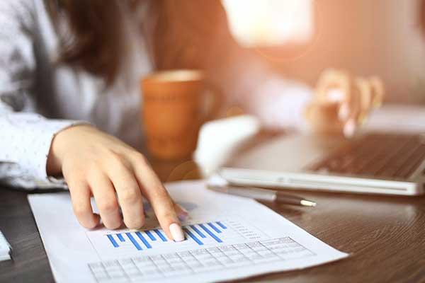 un uomo alla scrivania, con una mano scrive al computer e con l'altra indica un foglio con dei grafici blu