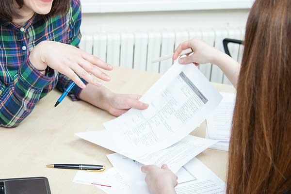due donne alla scrivania con dei fogli e un computer portatile stanno discutendo di lavoro