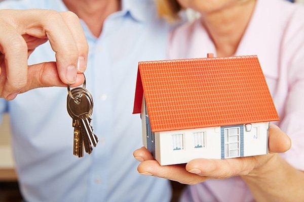 vista ravvicinata di un uomo con le chiavi in mano e di una donna con un  modellino di una casa