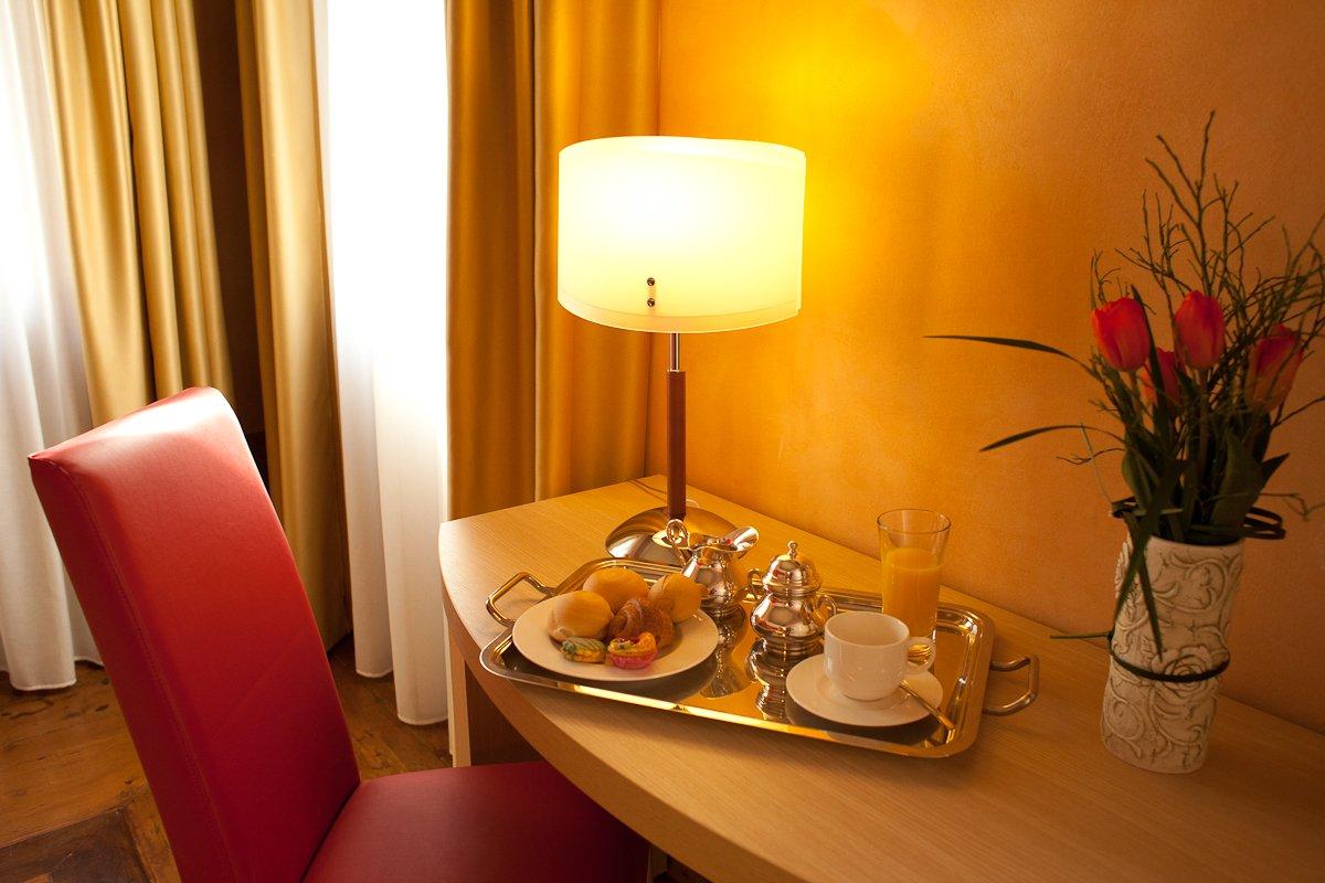 un vassoio con la colazione appoggiato su una scrivania