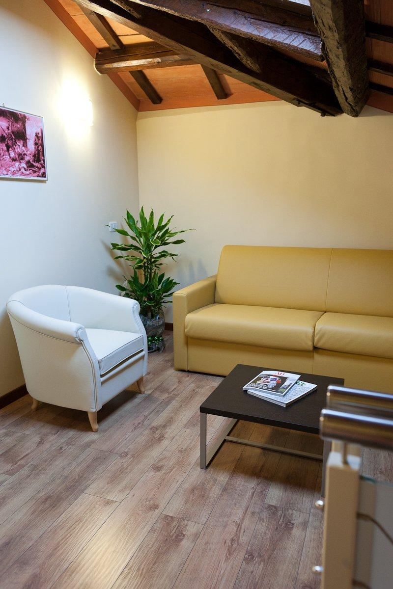 un divano giallo, una poltroncina bianca e un tavolino con delle riviste
