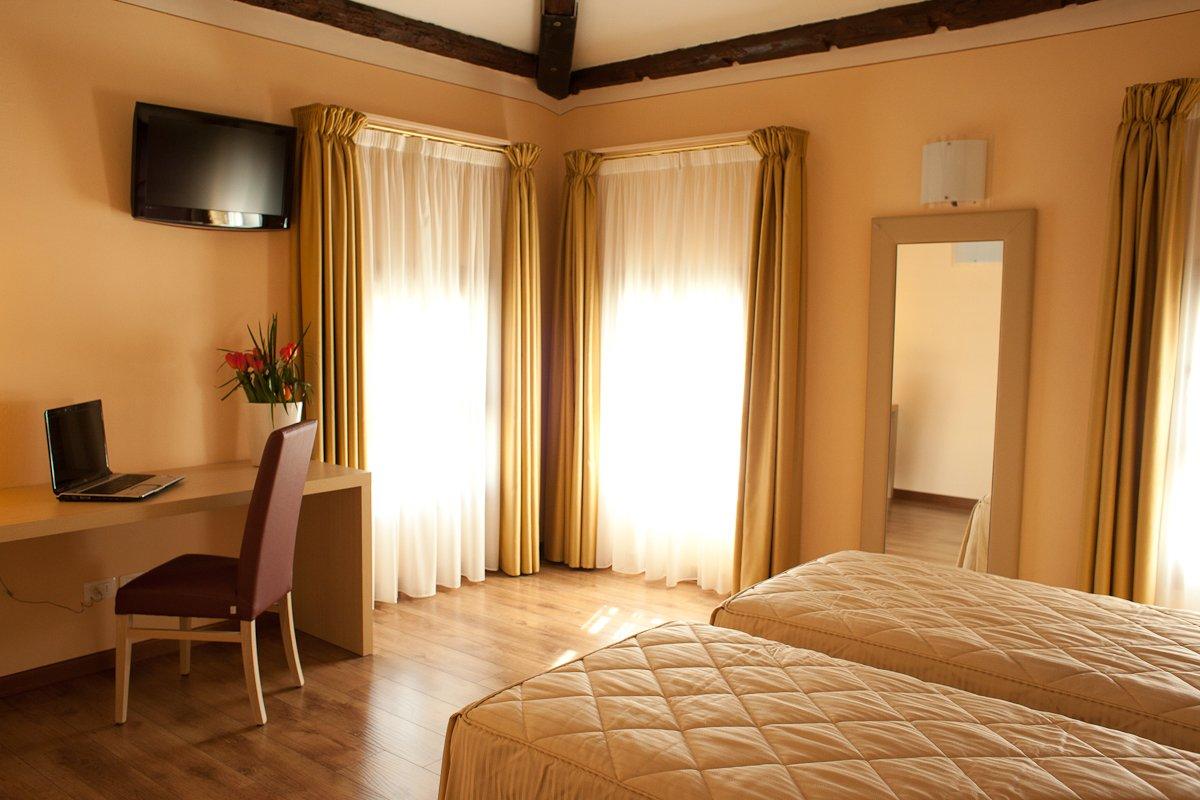 una camera d'hotel con 2 letti singoli e una scrivania con un computer