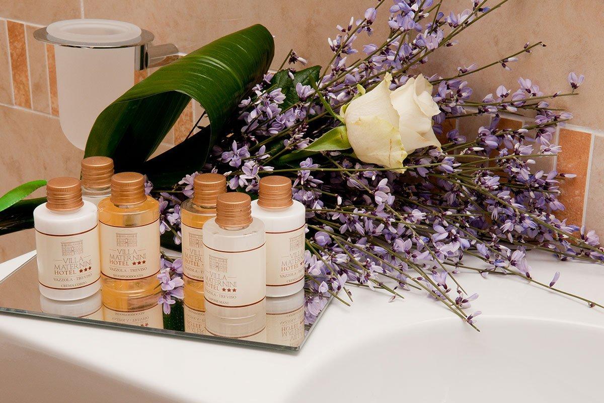 dei flaconi di bagnoschiuma e shampoo e una composizione di fiori
