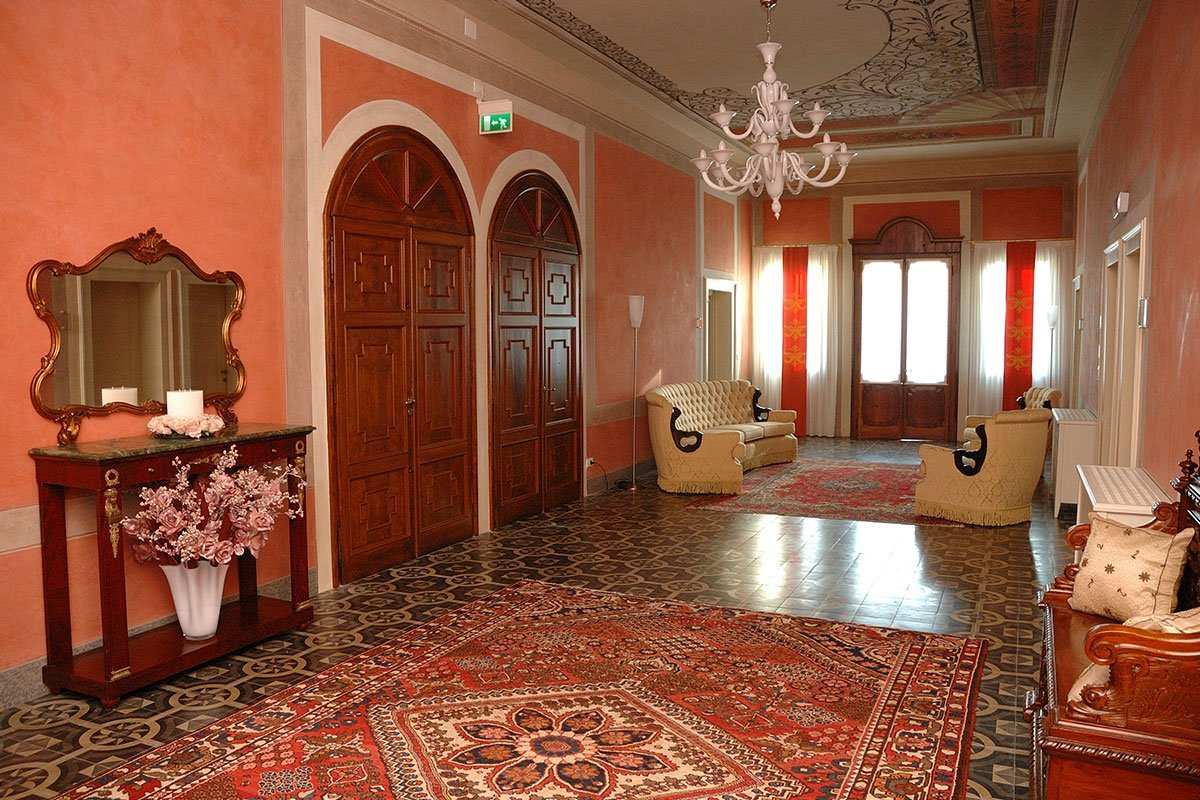 veduta interna di un albergo con porte rosse e muti color pesca