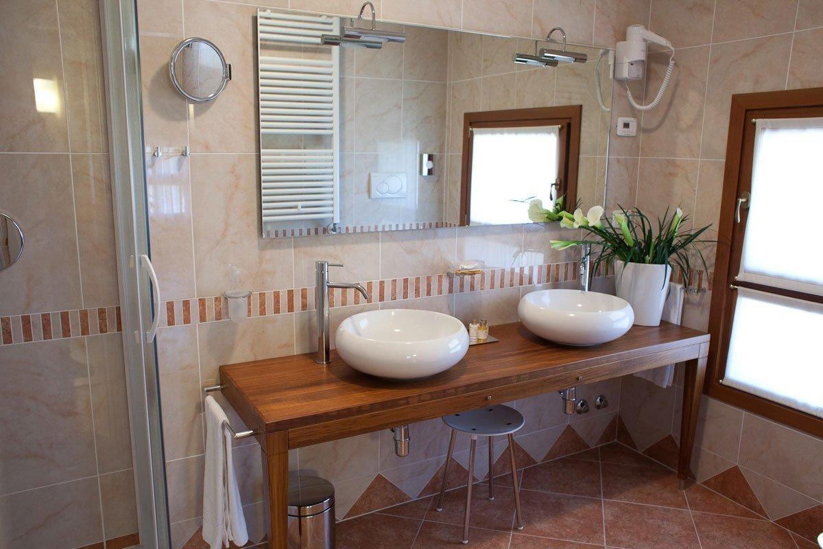 un bagno con due lavabi rotondi e un box doccia