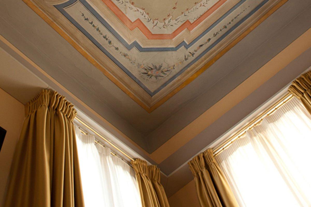 delle tende dorate e  bianche e un soffitto a disegni